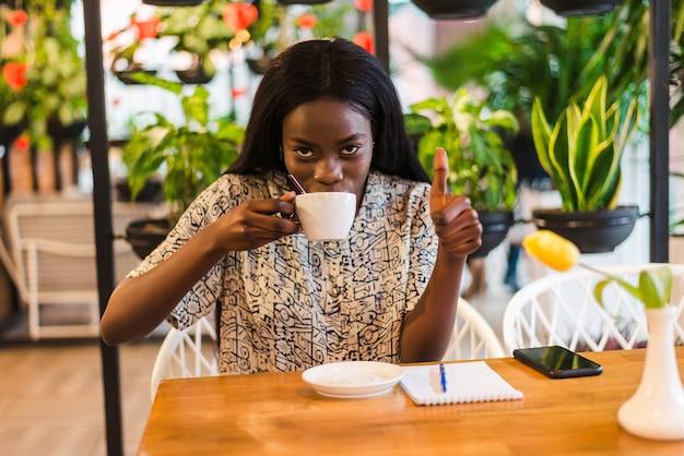 Kobieta sukcesu pokazuje kciuk w górę. afrykańska kobieta z filiżanką kawy i kciuki do góry uśmiechnięty w kawiarni