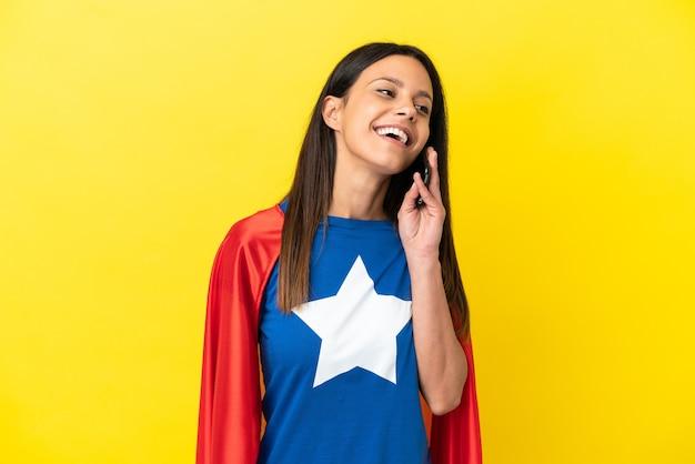 Kobieta super hero na żółtym tle prowadząca rozmowę z telefonem komórkowym z kimś
