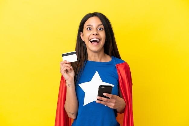 Kobieta super hero odizolowana na żółtym tle kupując za pomocą telefonu komórkowego i trzymając kartę kredytową ze zdziwionym wyrazem twarzy