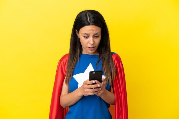 Kobieta superbohaterka na żółtym tle patrząca w kamerę podczas korzystania z telefonu komórkowego ze zdziwionym wyrazem twarzy
