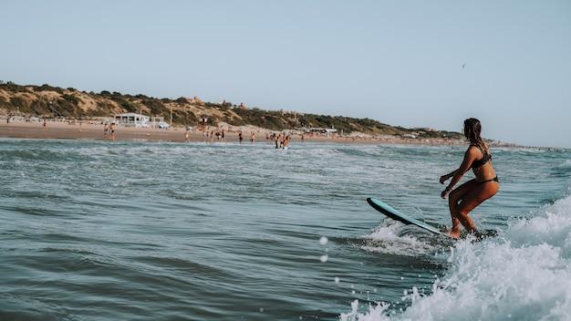 Kobieta surfuje na małych falach