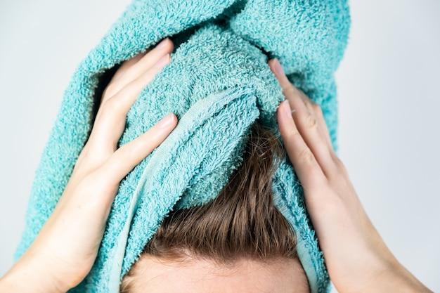 Kobieta susząca włosy ręcznikiem. zakończenie kobieta używa kąpielowego ręcznika do ręcznego suszenia włosów