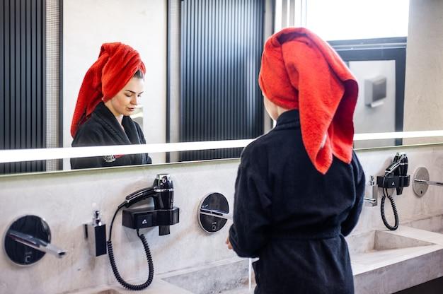 Kobieta susząca włosy w łazience