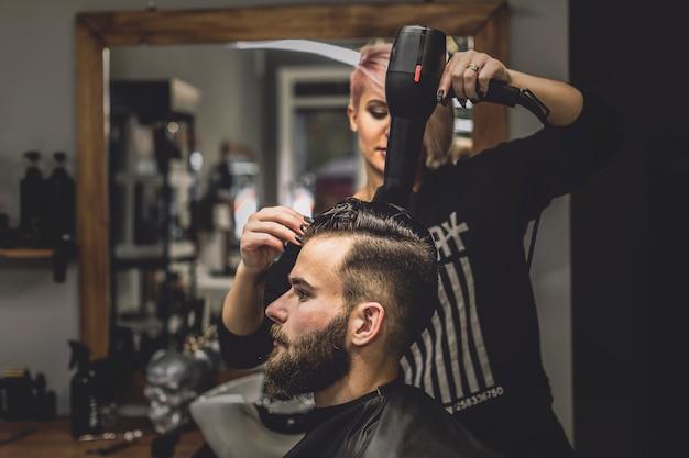 Kobieta suszarniczy włosy mężczyzna w zakładzie fryzjerskim