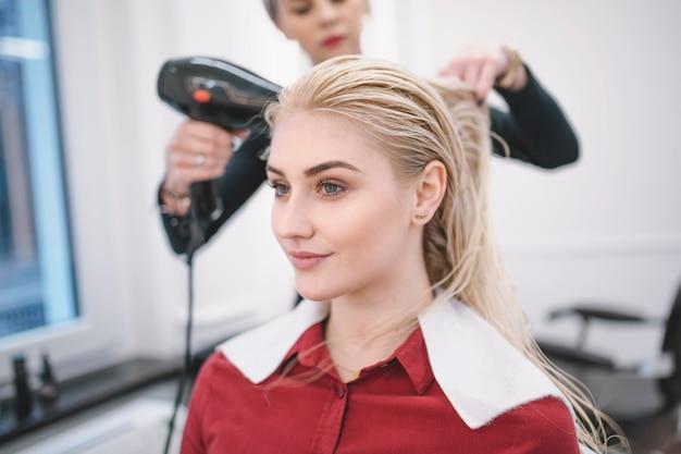 Kobieta suszarniczy włosy młoda dziewczyna