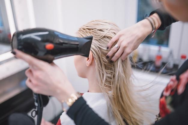 Kobieta suszy mokrego włosy klient