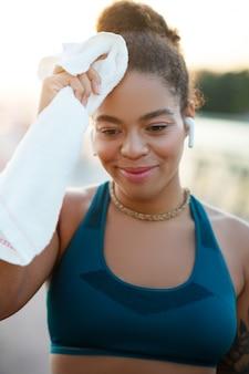 Kobieta suszy pot. młoda afroamerykanka suszy pot na czole po intensywnym biegu