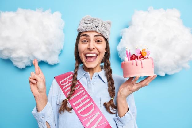 Kobieta świętuje urodziny składa życzenie przed zdmuchnięciem świeczek na świątecznym torcie trzyma skrzyżowane palce nosi maskę do spania i koszulę odizolowane na niebiesko