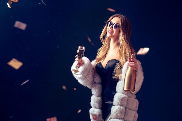 Kobieta świętuje z szampanem w okularach przeciwsłonecznych