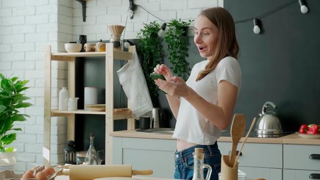 Kobieta świętuje zwycięstwo lub zwycięstwo online na smartfonie stojącym w kuchni