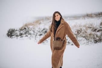 Kobieta szczęśliwa w płaszczu w zimie na zewnątrz w parku