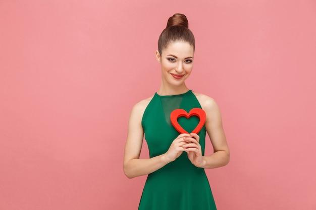 Kobieta szczęścia trzymająca czerwone serce i uśmiechnięta