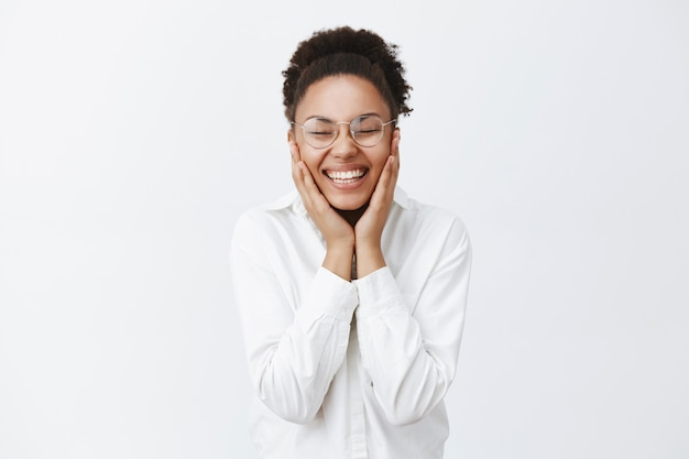 Kobieta szczęśliwa, mogąca pozbyć się trądziku, dotykająca pięknej i naturalnej skóry, trzymająca dłonie na policzkach i uśmiechająca się beztrosko od zachwytu i przyjemności, stojąca w okularach i białej koszuli na szarej ścianie