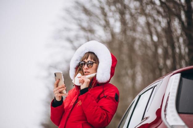 Kobieta szczęśliwa opowiada na telefonie outside samochodem w zimie