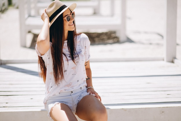 Kobieta szczęśliwa w kapeluszu przy plażą