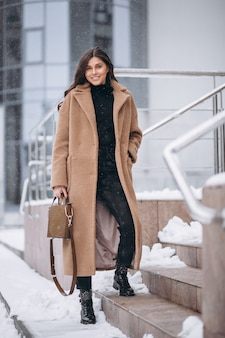 Kobieta szczęśliwa w płaszczu w zimie na zewnątrz