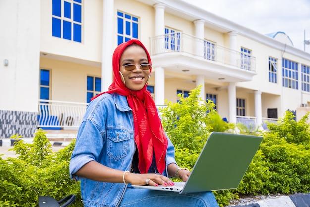 Kobieta szczęśliwie przeglądania internetu za pomocą laptopa siedząc w parku