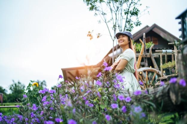 Kobieta szczęśliwie stoi w ogrodzie kwiatowym w drewnianych balustradach