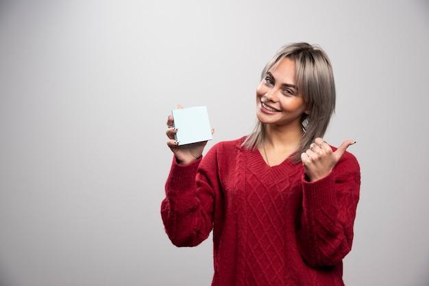 Kobieta szczęśliwie trzymając notatnik i dając kciuk w górę.