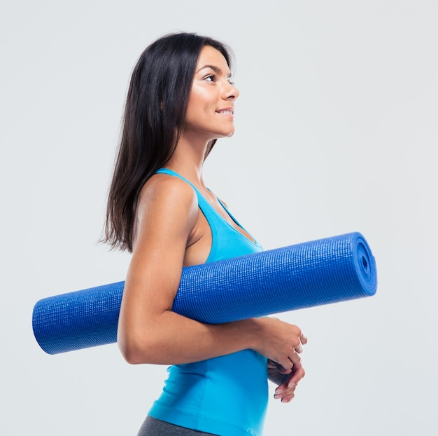 Kobieta szczęśliwy sportowych trzymając matę do jogi