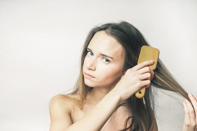 Kobieta szczotkująca swoje długie włosy z aeans na białym tle, odosobniona
