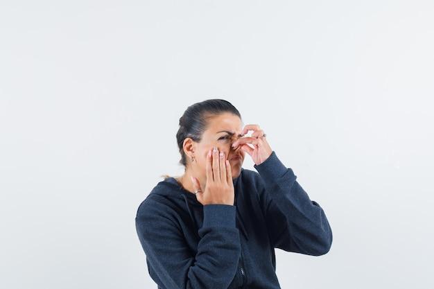 Kobieta szczypiąca nos w bluzie z kapturem i wyglądająca na zniesmaczoną. przedni widok.
