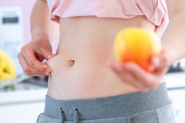 Kobieta szczypie nadmiar tłuszczu w talii i zyskuje dodatkowe kilogramy. koncepcja nadwagi. zacznij jeść zdrowe, zrównoważone, czyste jedzenie