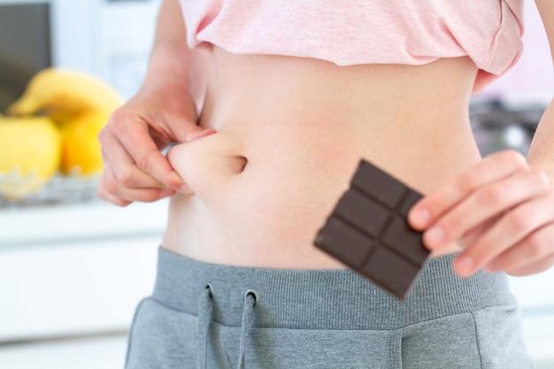 Kobieta szczypie nadmiar tłuszczu w talii i zyskuje dodatkowe kilogramy z powodu niezdrowego słodkiego węglowodanów