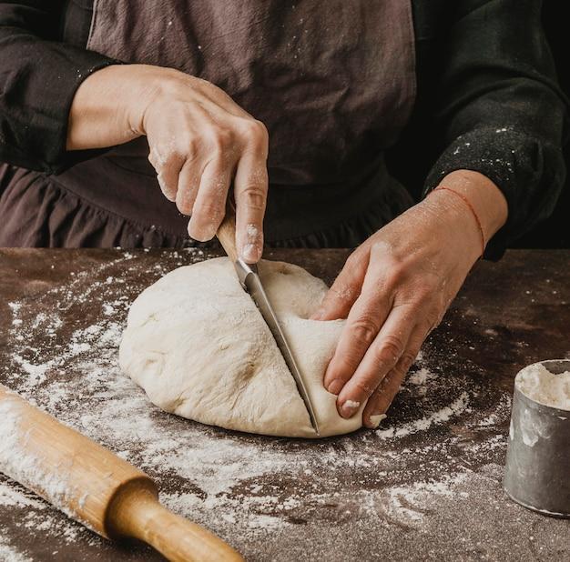 Kobieta szef kuchni cięcia ciasta na pizzę na pół