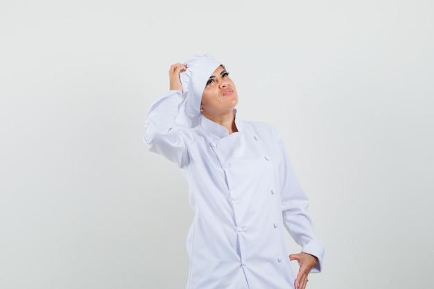 Kobieta szef kuchni drapie się po głowie, patrząc w biały mundur i patrząc niepewnie