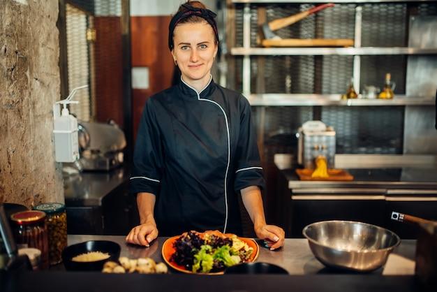 Kobieta szef kuchni gotuje sałatkę mięsną na drewnianym stole. dekorowanie na befsztyk, przygotowanie potraw w kuchni