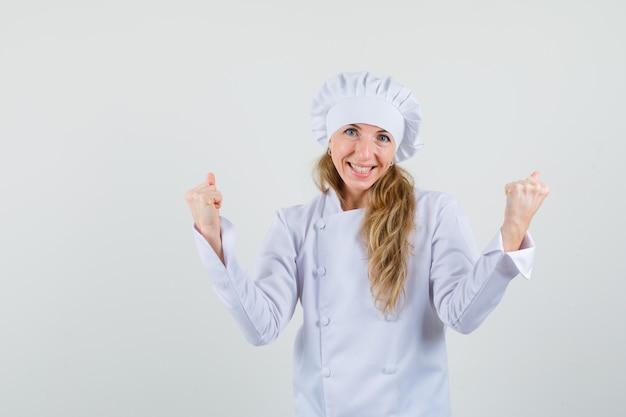 Kobieta szef kuchni pokazując gest zwycięzcy w białym mundurze i wyglądający na błogi