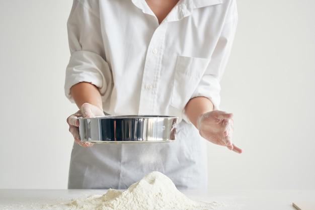 Kobieta szef kuchni przesiewa mąkę na stole piekarnia gotowanie ciasta past