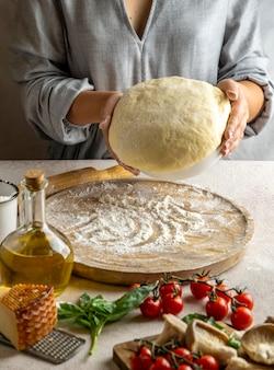 Kobieta szef kuchni przygotowuje ciasto na pizzę