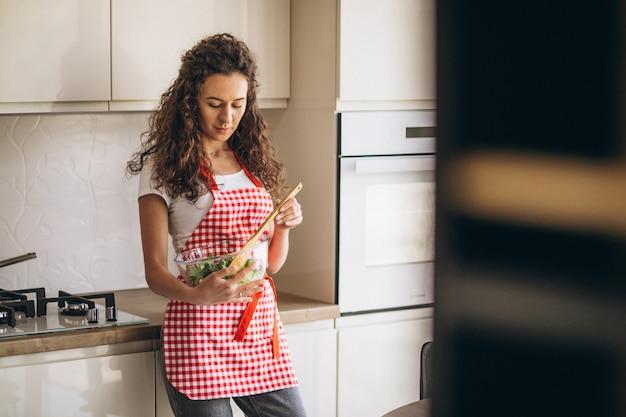 Kobieta szef kuchni robi sałatki przy kuchnią