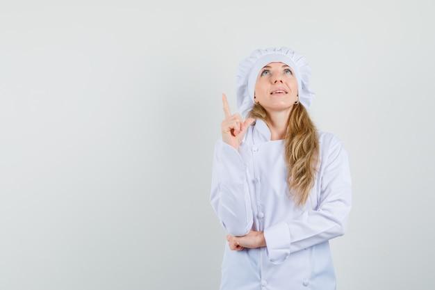 Kobieta szef kuchni skierowaną w górę w białym mundurze i patrząc z nadzieją
