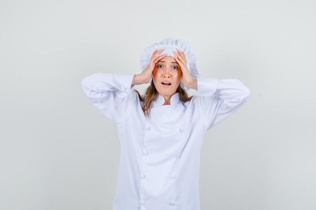 Kobieta szef kuchni trzymając głowę rękami w białym mundurze i wyglądający na zmęczonego