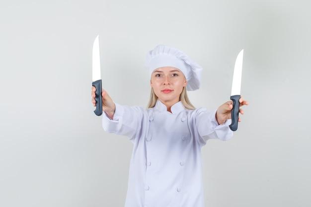 Kobieta szef kuchni trzymając noże i uśmiechając się w białym mundurze