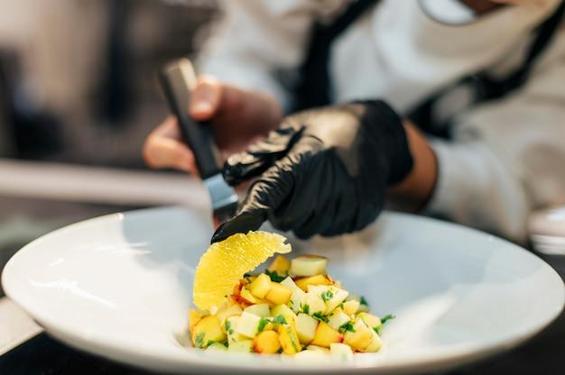 Kobieta szef kuchni umieszcza plasterek pomarańczy na naczyniu