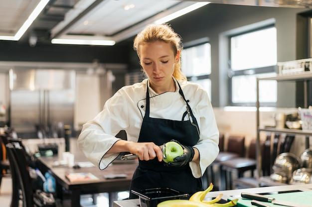 Kobieta szef kuchni usuwa skórkę jabłka