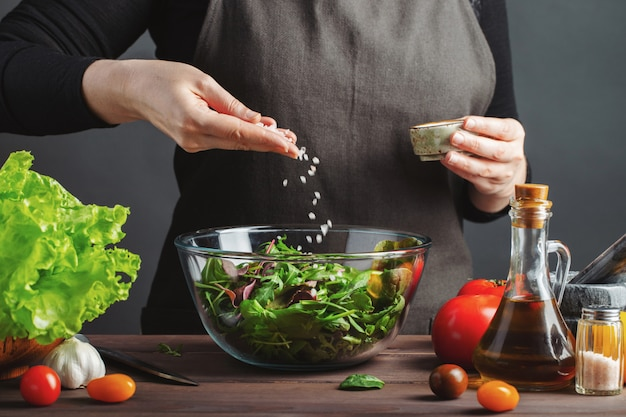 Kobieta szef kuchni w kuchennej narządzanie sałatce.