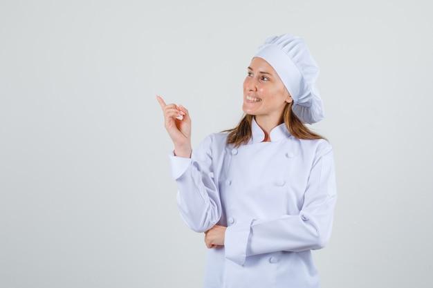 Kobieta szef kuchni wskazując, patrząc na bok w białym mundurze i wyglądający wesoło