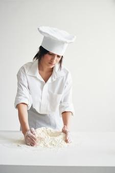 Kobieta szef kuchni wyrabia ciasto pracując z profesjonalną mąką