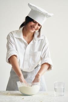 Kobieta szef kuchni wyrabia ciasto profesjonalne produkty mączne do gotowania