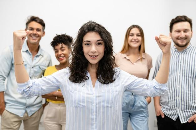 Kobieta szef potężny gest silnych muskularnych kolegów z tyłu w coworkingu