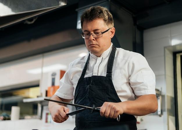 Kobieta szefa kuchni do ostrzenia noży w kuchni