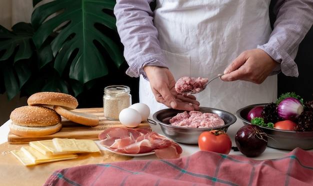 Kobieta szefa kuchni gotuje duży burger lub cheeseburger i trzyma mięso mielone.