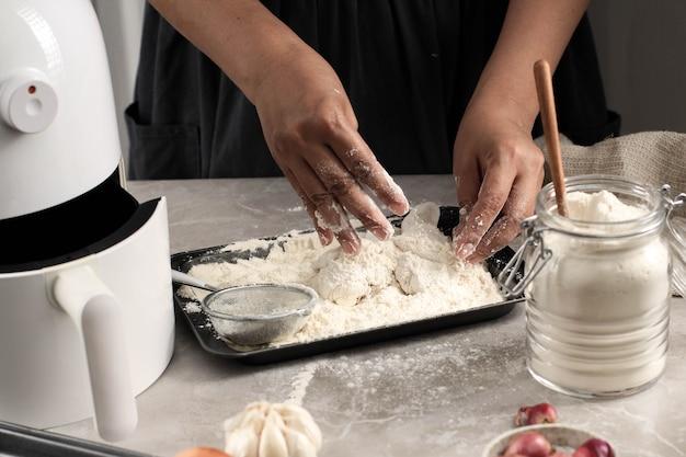 Kobieta szefa kuchni robi domowe chrupiące smażonego kurczaka, panierowanie poduszek z kurczaka z mąką w kuchni, wybrane fokus