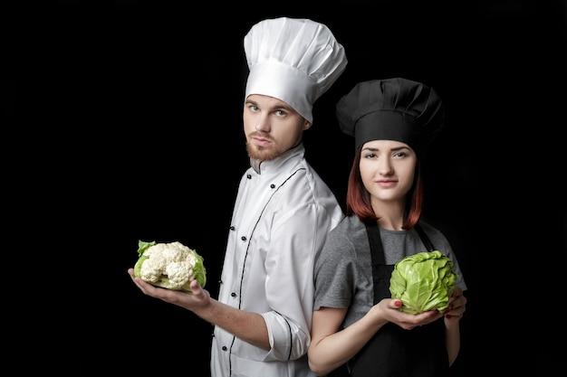 Kobieta szefa kuchni w czarnym mundurze i mężczyzna szef kuchni w białym mundurze trzymają świeżą zieloną kapustę i kalafior...
