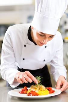 Kobieta szefa kuchni w kuchni gotowania w restauracji